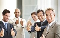 Group of successful business colleagues showing their thumbs and smiling